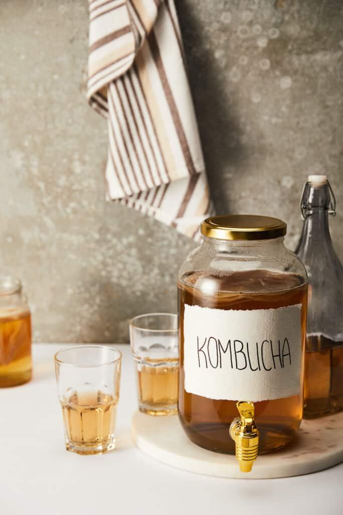 jar with kombucha near glasses on textured grey background with striped napkin
