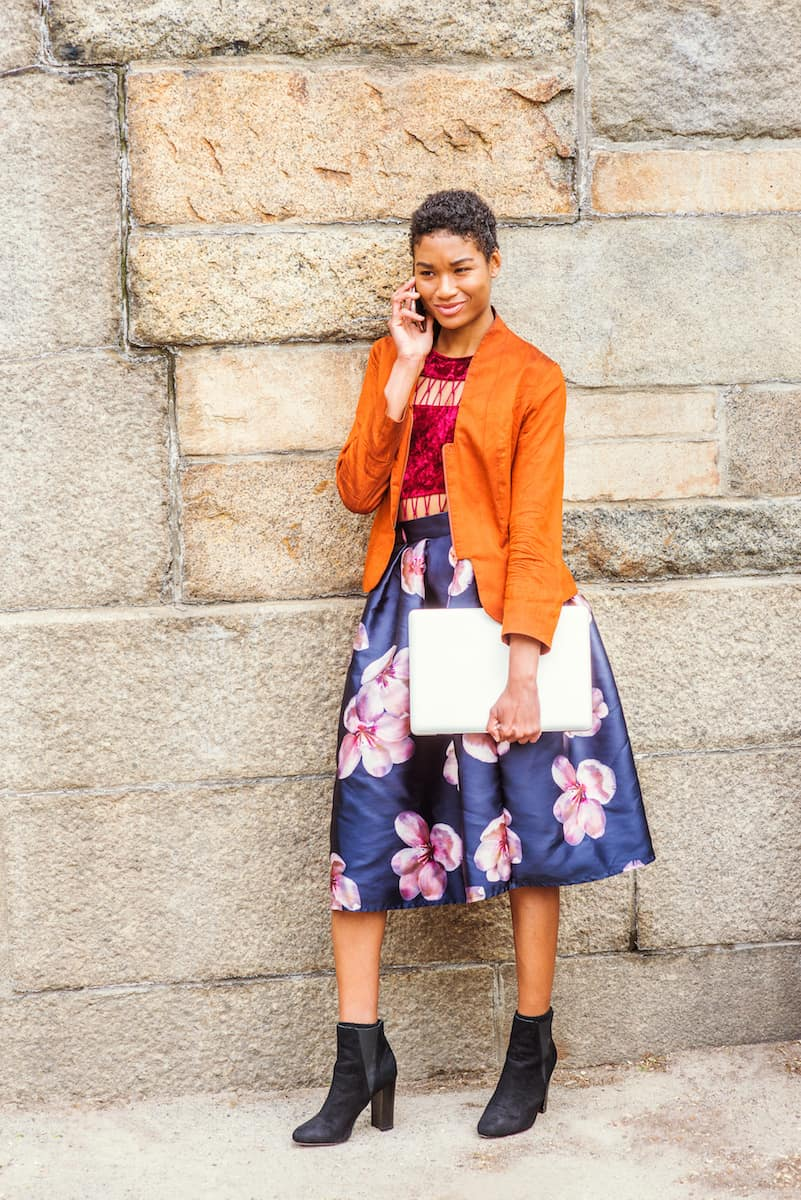 Young African American Woman talking on cell phone outside in New York City, wearing orange red jacket, flower patterned skirt, black boot shoes, carrying laptop computer, standing by stone wall wearing wide width shoes