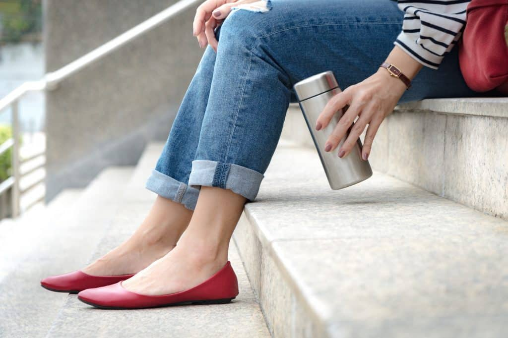 Crop shot of an attractive woman wearing jeans with stylish ruby red flat shoes sitting on a stairs, her hand grab a reusable isolated water bottle. Plastic-free, No straw, Eco, Zero waste concept.