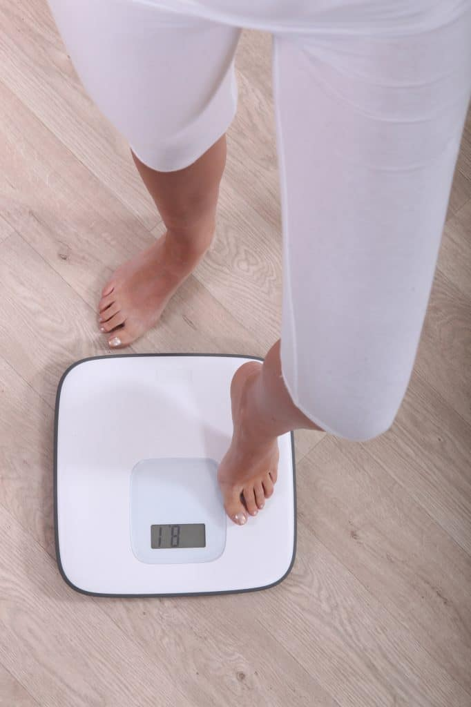 woman stepping on a scale to weigh herself noom peloton