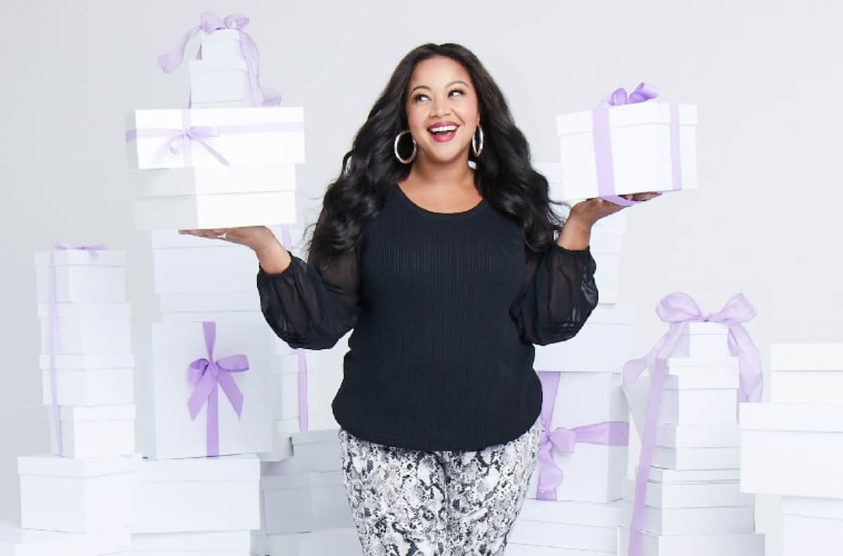 african american woman surrounded by white boxes with purple ribbons from dia&co subscription box styling service