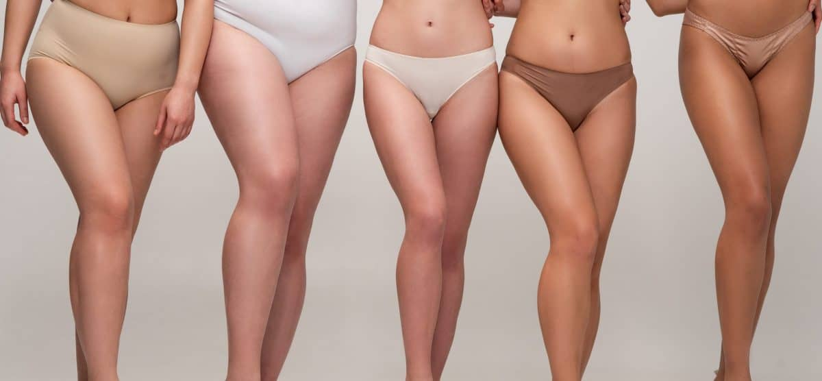 cropped view of five multicultural women in underwear and sneakers, body positivity concept menstrual lingerie