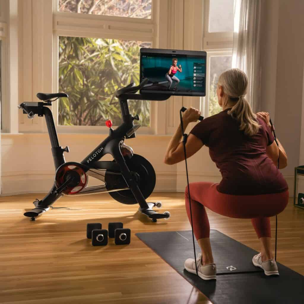 older woman working out with resistance bands in front of peloton bike plus with instructor jess sims