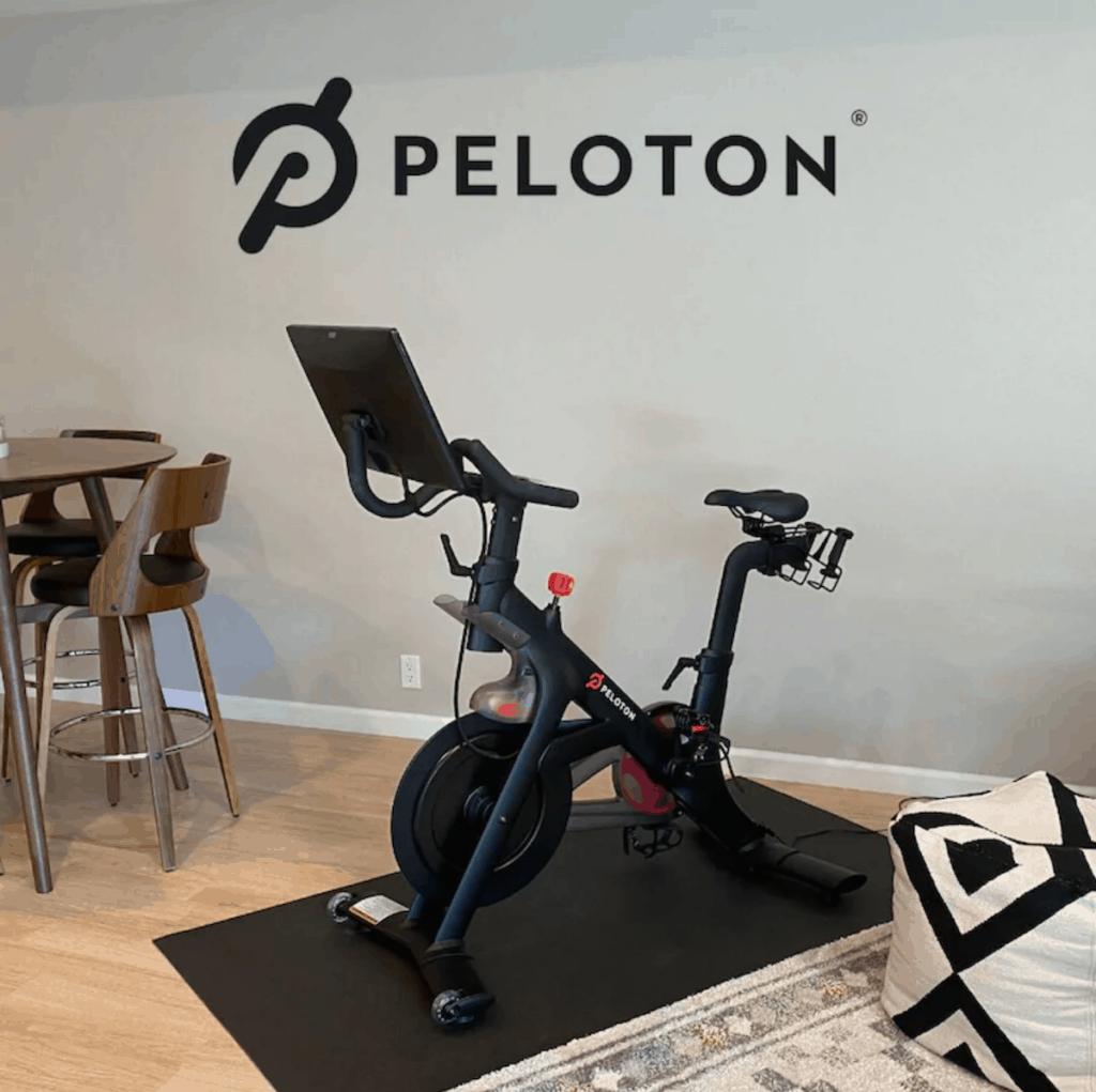 Peloton bike in front of Peloton decal.
