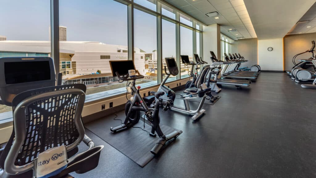 Hotel fitness center with spin bikes in front of windows.