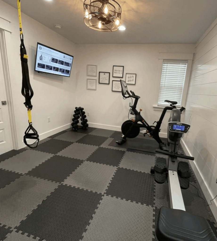 Exercise room with Peloton and rower.